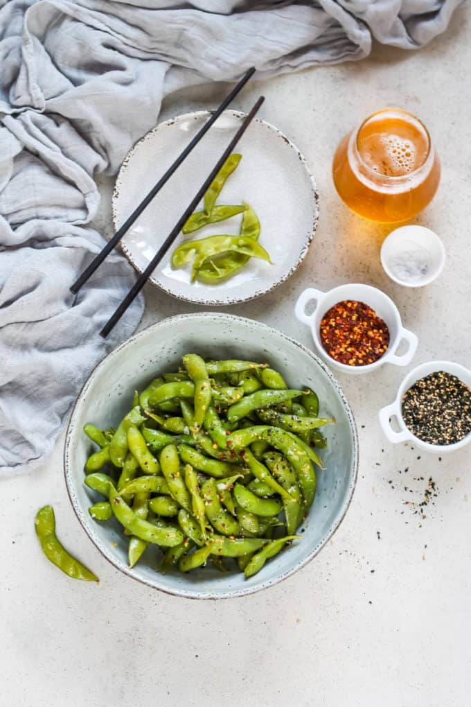 overhead photo of spicy garlic edamame with a glass of beer and some edamame pods on a grey background