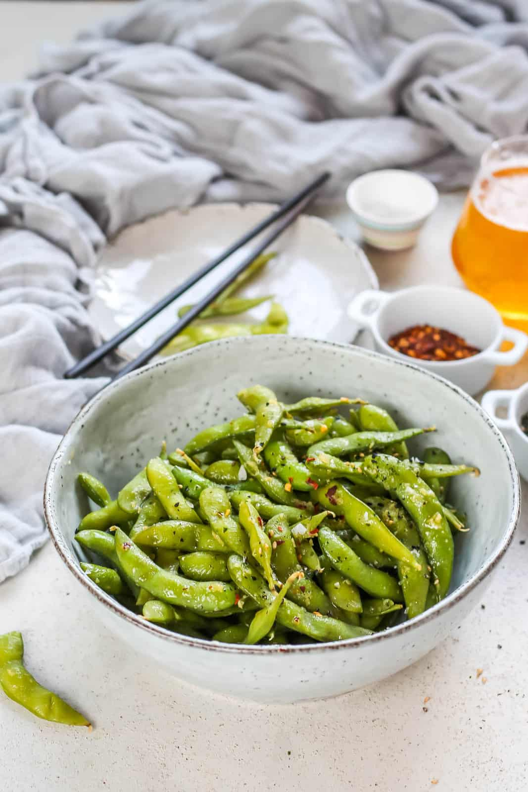 a bowl of spicy edamame with some beer and chili flakes in the background