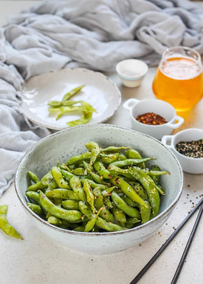 spicy garlic edamame in a blue bowl with some beer and edamame pods in the background