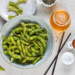 a bowl of spicy edamame with a pair of black chopsticks to the side