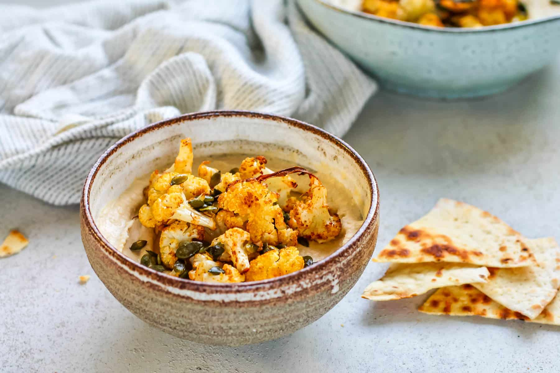 a ceramic bowl with hummus and roasted cauliflower
