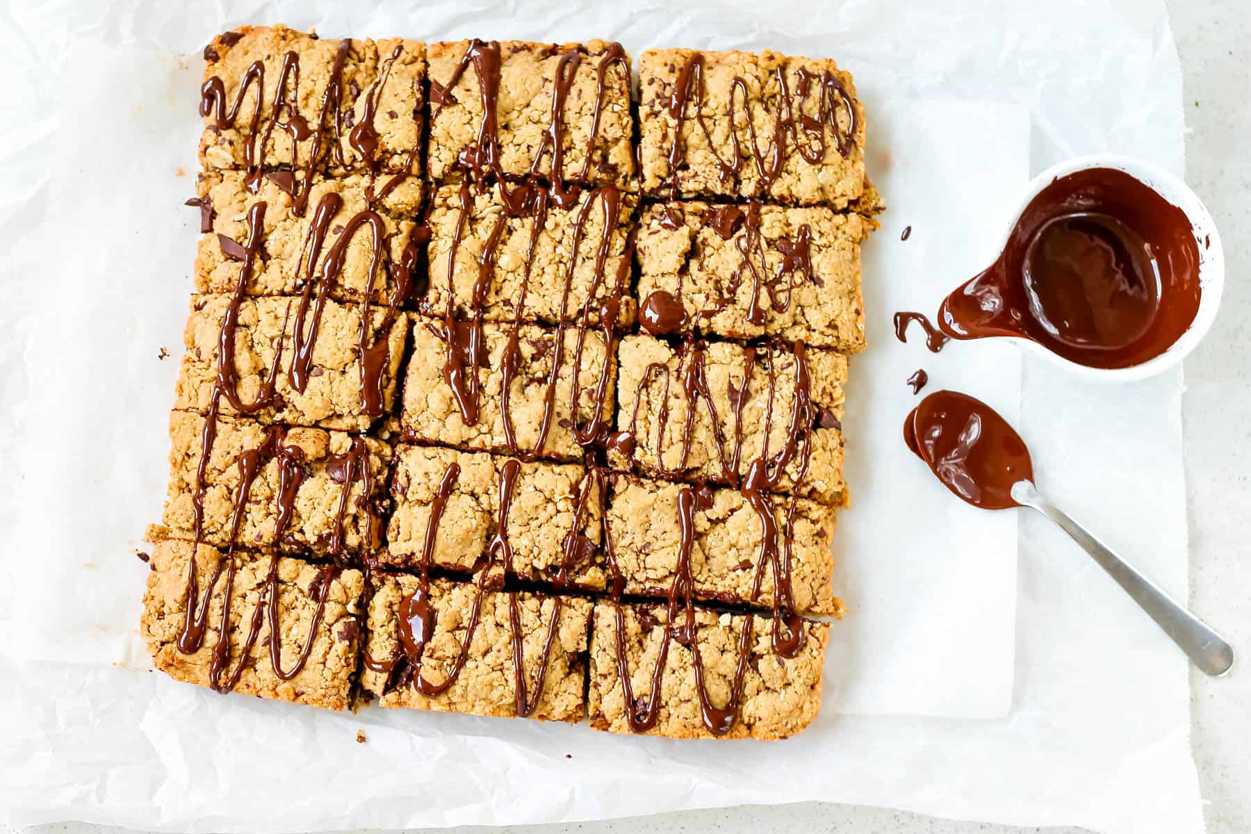 peanut butter oat bars on a sheet of parchment paper with melted chocolate to the side