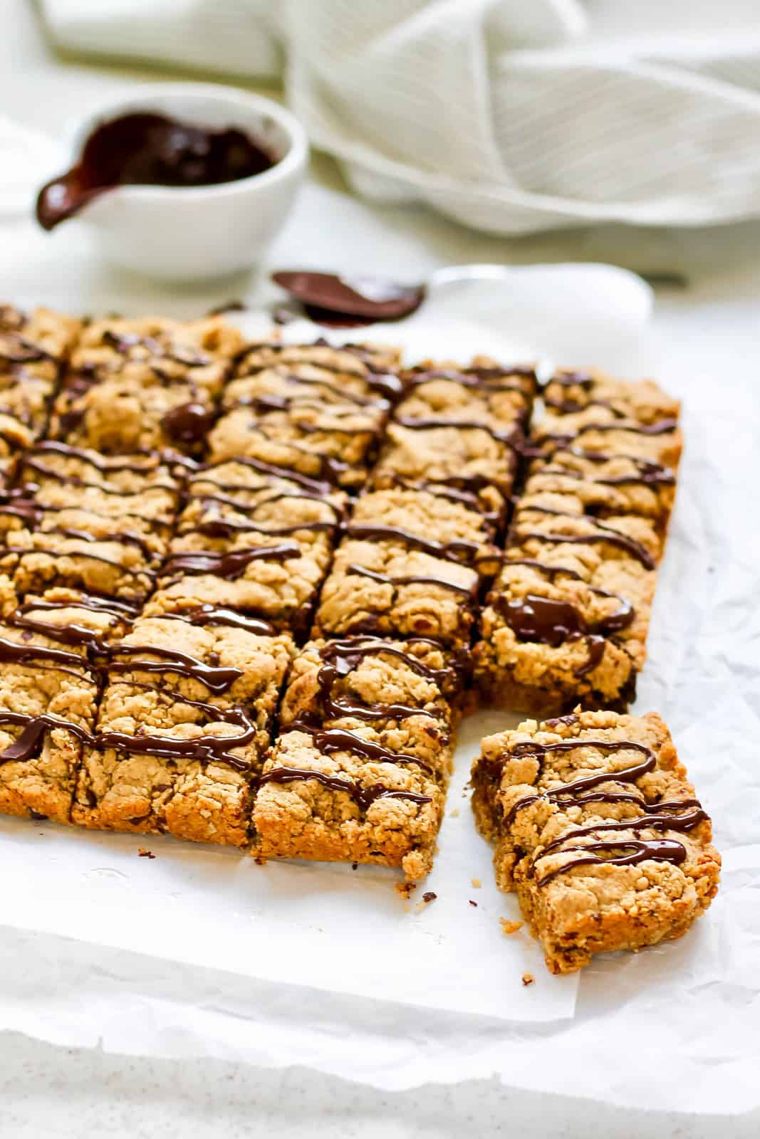 close up photo of peanut butter oat bars on a marble slab with one bar askew