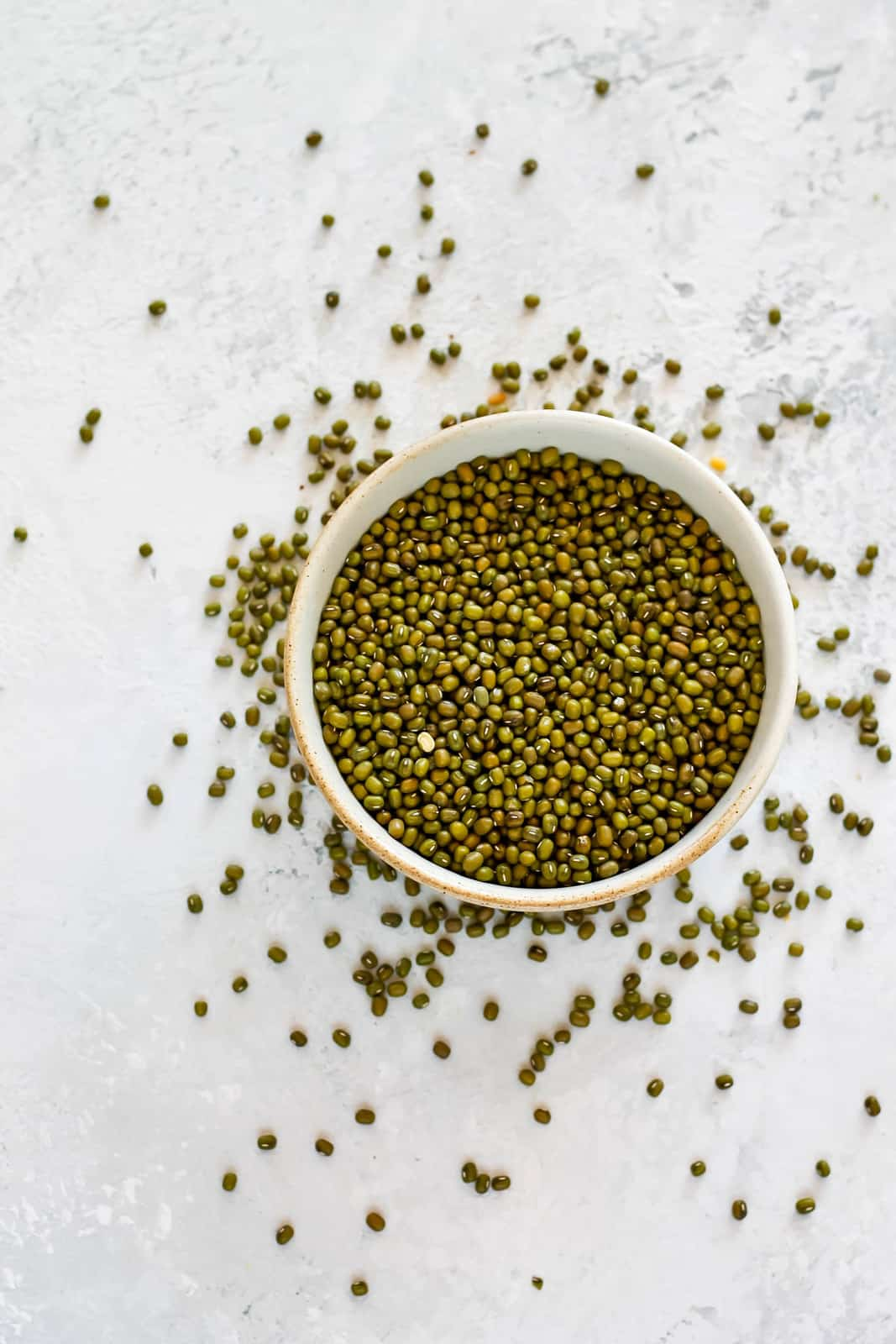 overhead photo of mung beans in a bowl with scattered beans in the background