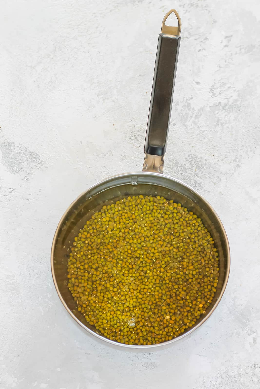 mung beans and water in a metal pot