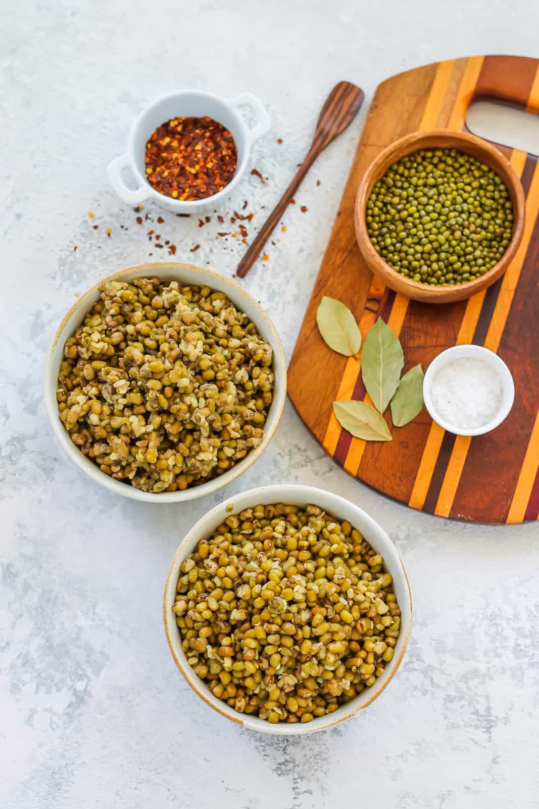two bowls of cooked mung beans on a grey background with some herbs and spices to the side