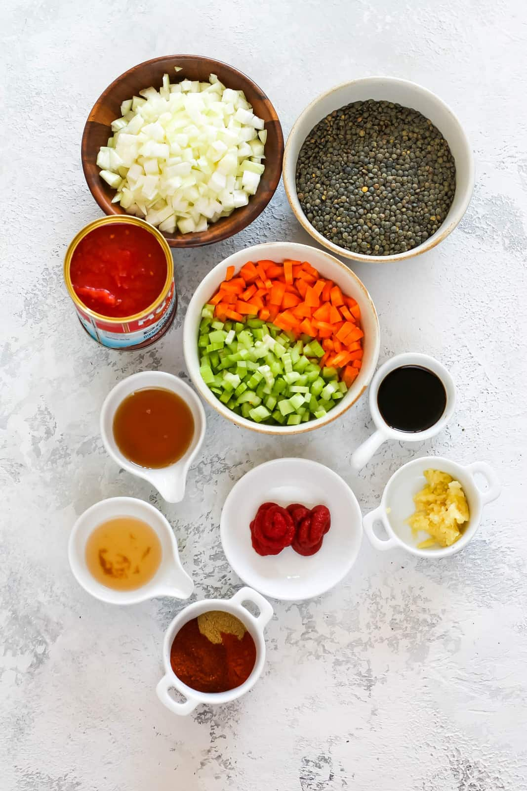 lentils, onions, carrots, celery, garlic, tomato paste, crushed tomatoes, soy sauce, and spices on a grey background