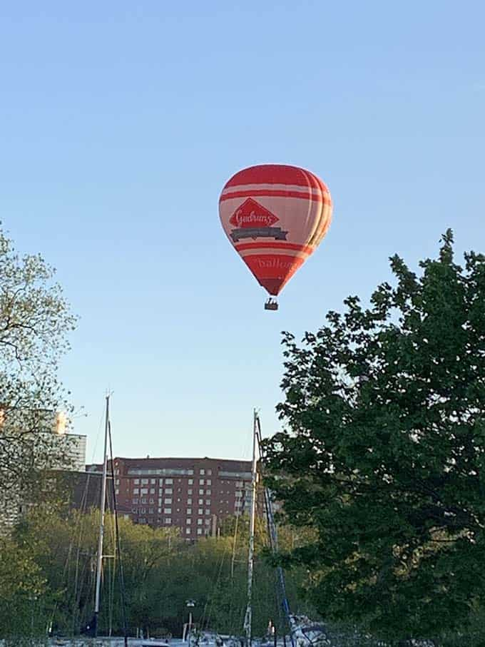 a red hot air balloon floating above some trees