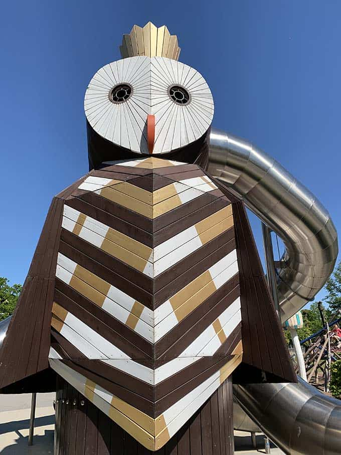 a giant wooden owl with a tunnel slide coming out of the side