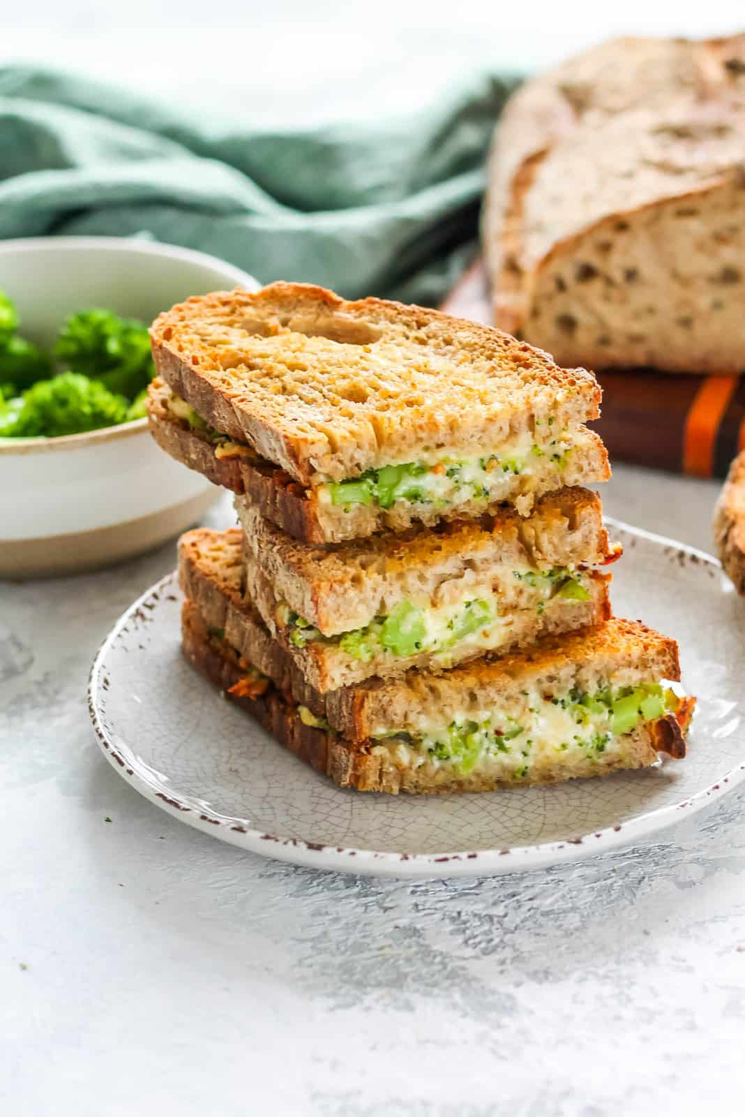 A broccoli grilled cheese sandwich stacked up on a white plate