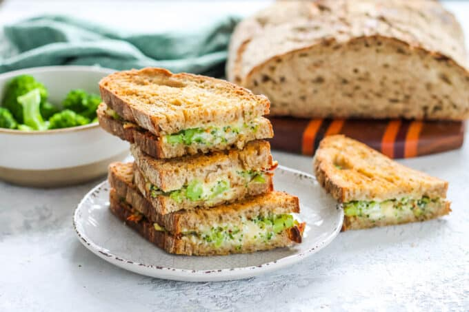 three broccoli grilled cheese sandwiches stacked up on a white plate