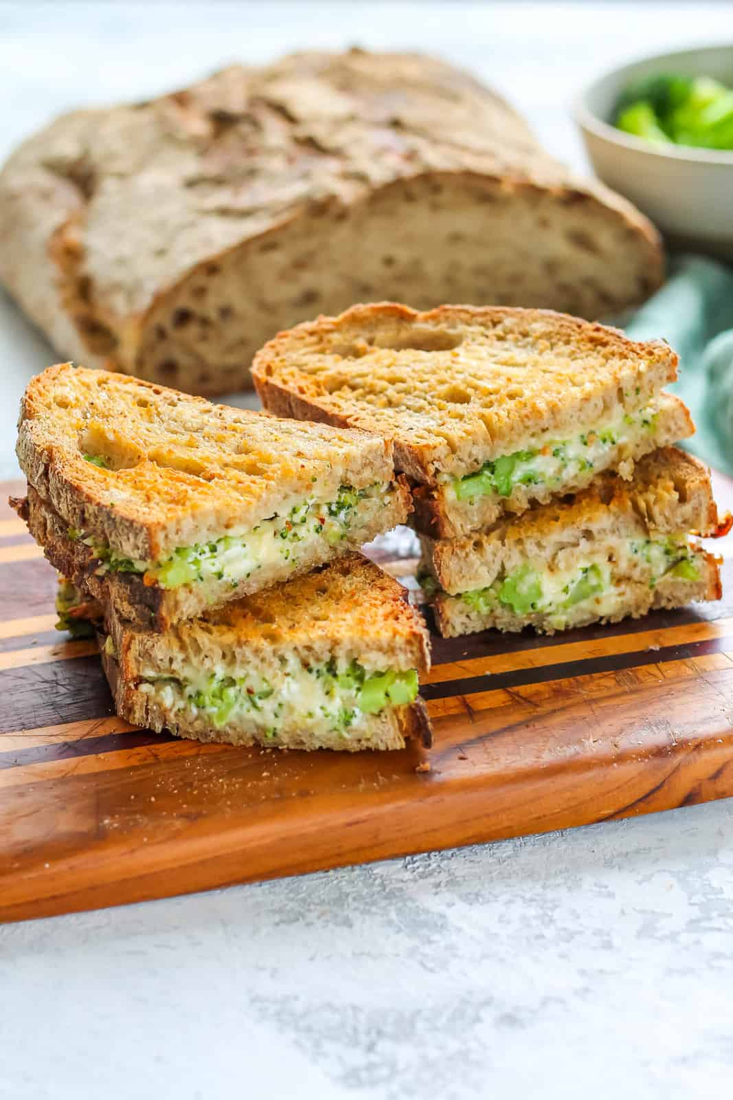 Two sliced broccoli grilled cheese sandwiches stacked on a wooden cutting board