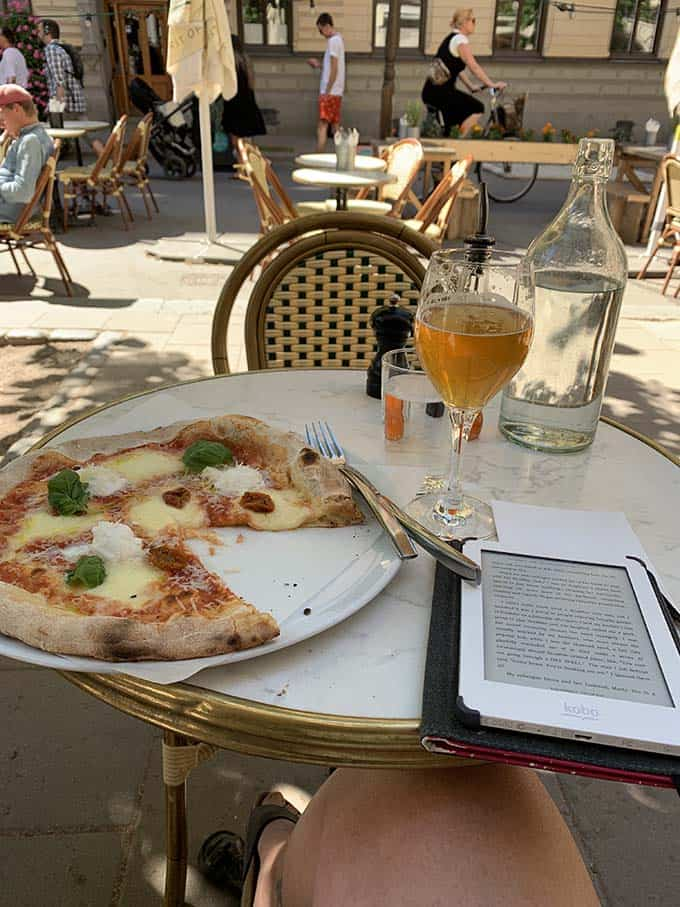 a pizza, glass of beer, and e-reader on a cafe table