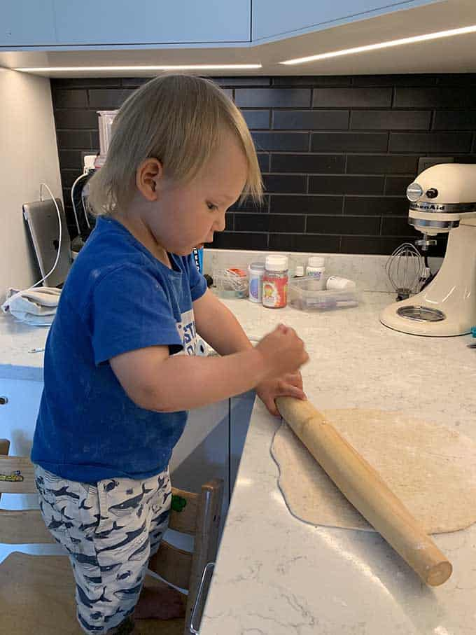 A toddler playing with a rolling pin in the kitchen