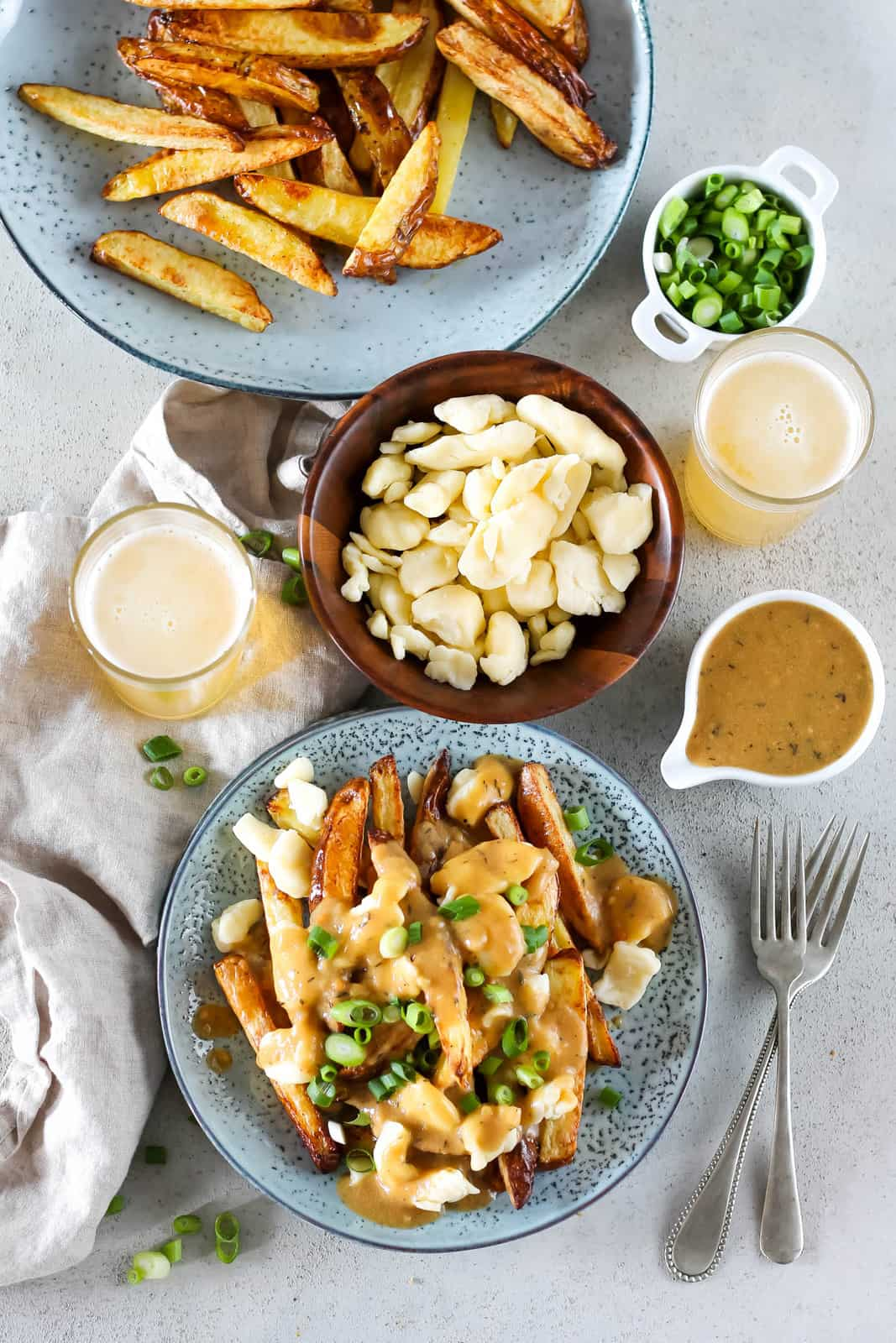 overhead photo of vegetarian poutine on a blue plate, together with all of the fixings to make poutine (fries, gravy, cheese curds)