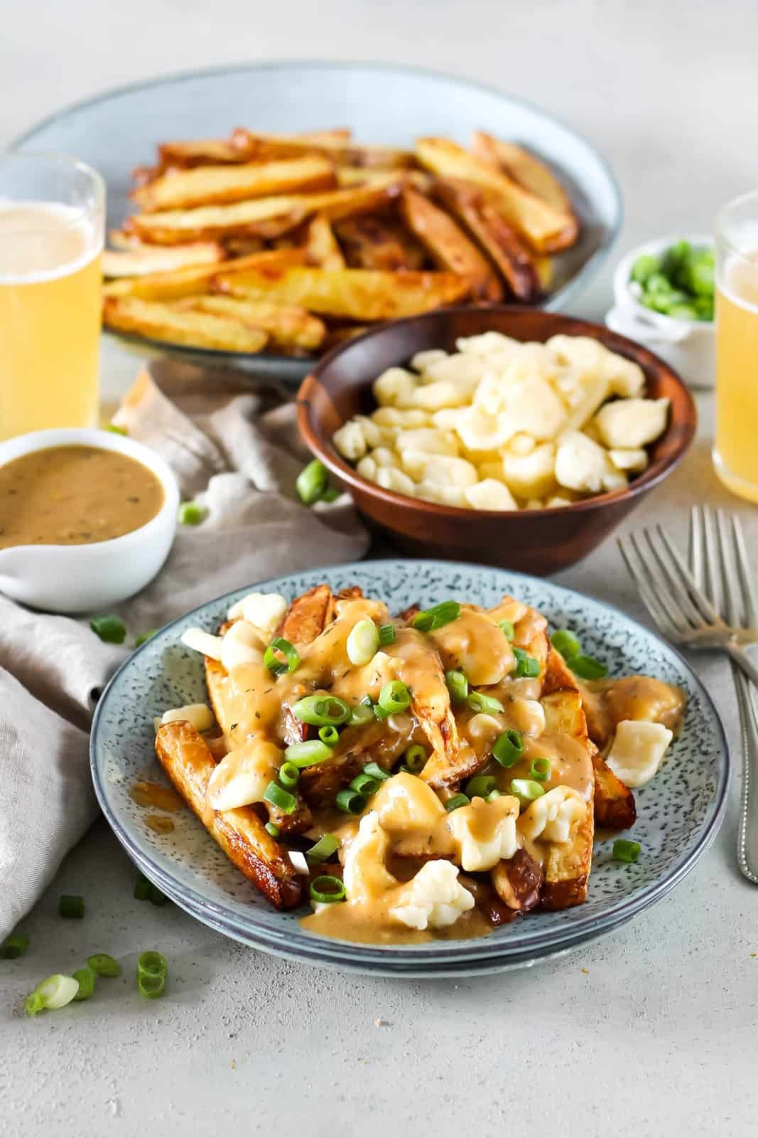 a blue plate with vegetarian poutine topped with green onions, with more fries, gravy, and cheese curds in the background