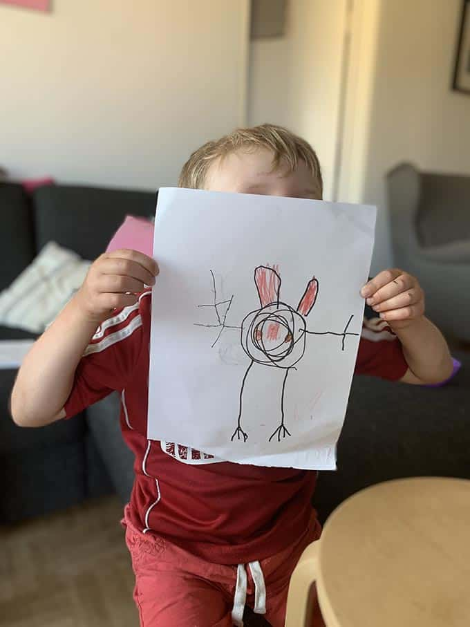 a boy in a red shirt holding a drawing of a bunny