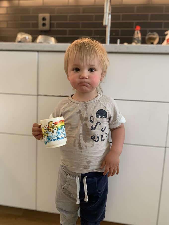 A small boy holding a mug of hot chocolate