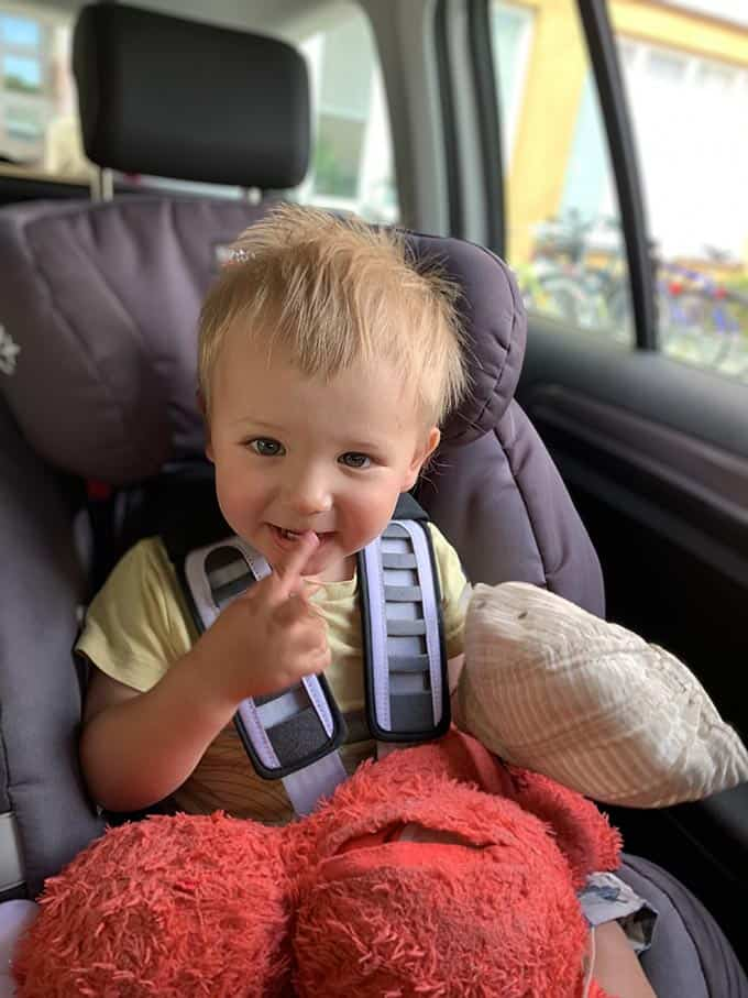 a boy in a car seat with an elmo toy