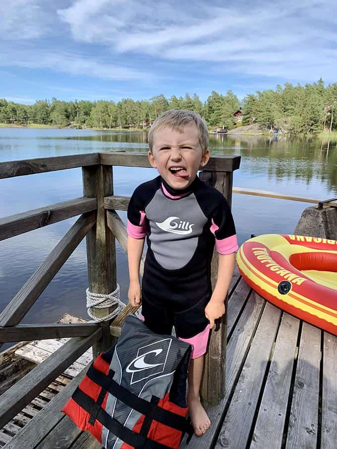 a boy standing on a dock in a pink and black wetsuit