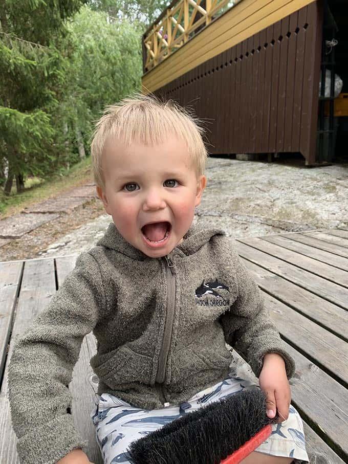 a boy sitting on a wooden deck in a brown fleece