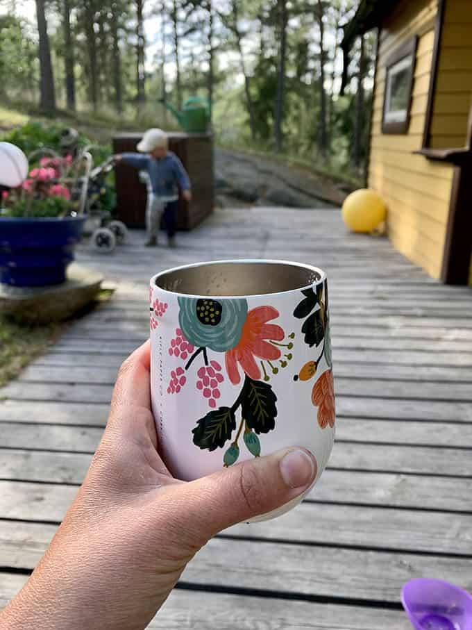 a flower-patterned drinking glass held in a woman's hand with a backyard patio in the background