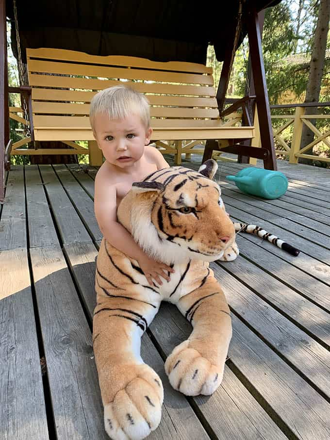 a small boy on top of a large stuffed tiger