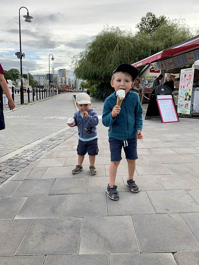 two boys eating ice cream cones on a sidewalk