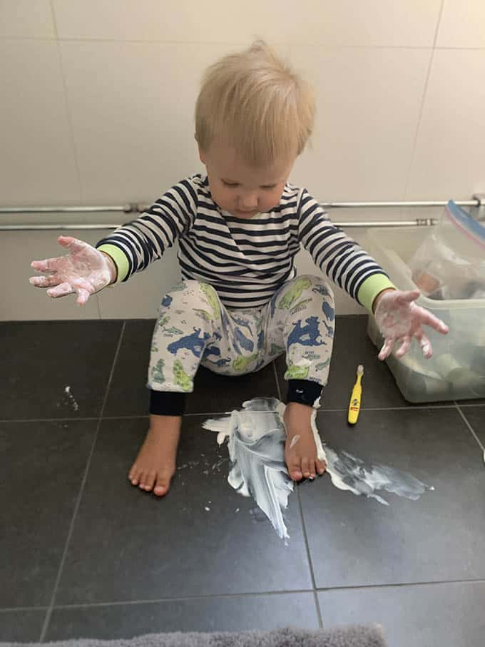 a boy on the bathroom floor with toothpaste smeared on the floor and his feet and hands