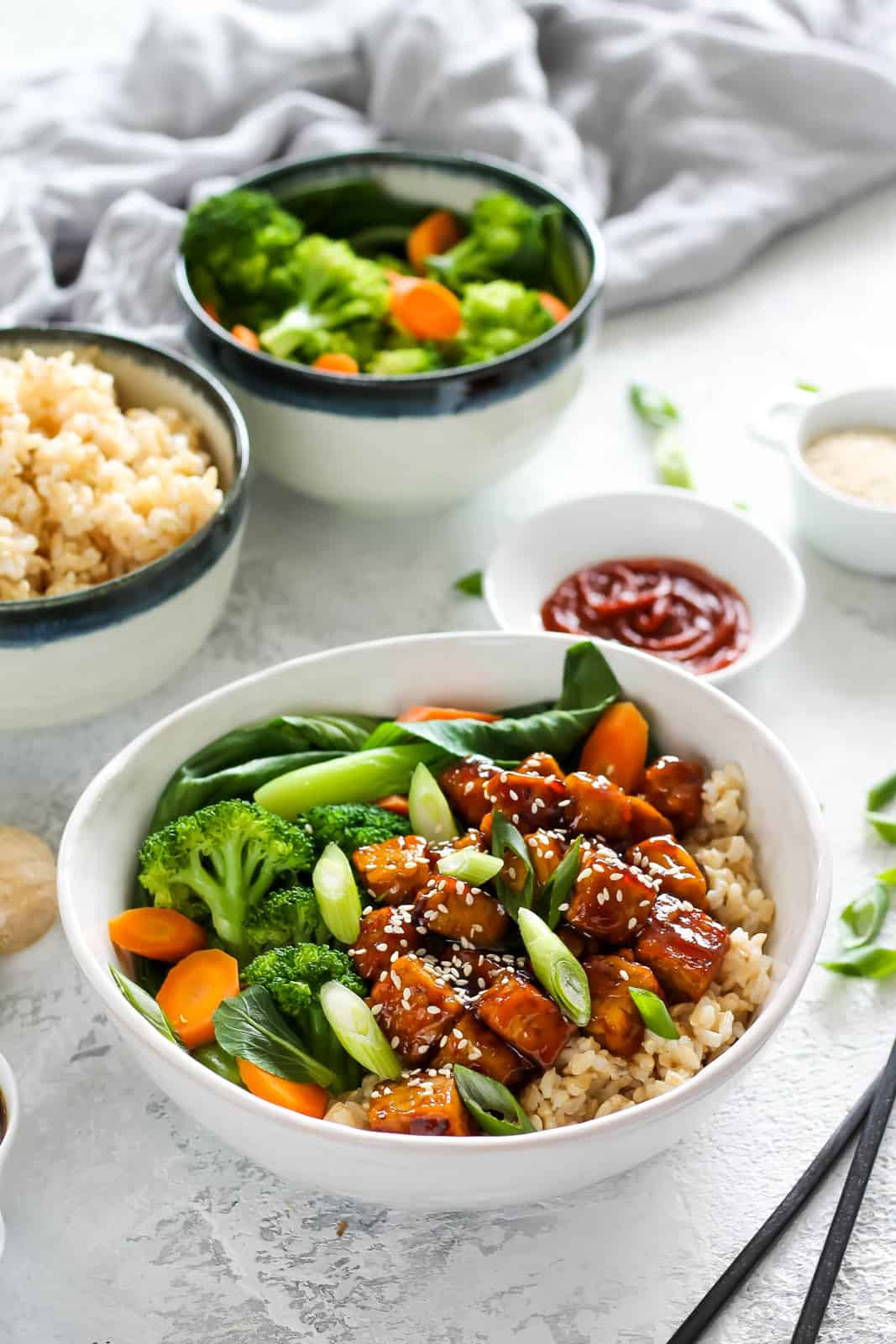 close up photo of a teriyaki tempeh bowl with brown rice and mixed vegetables and a pair of black chopsticks to the side