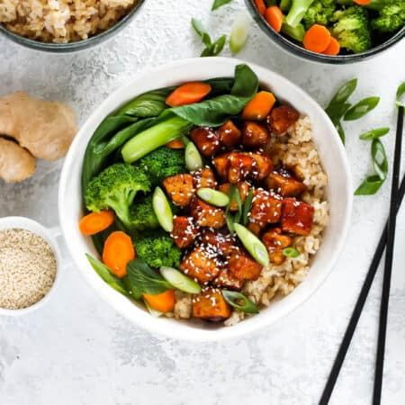 overhead photo of teriyaki tempeh in a white bowl with a pair of black chopsticks to the side