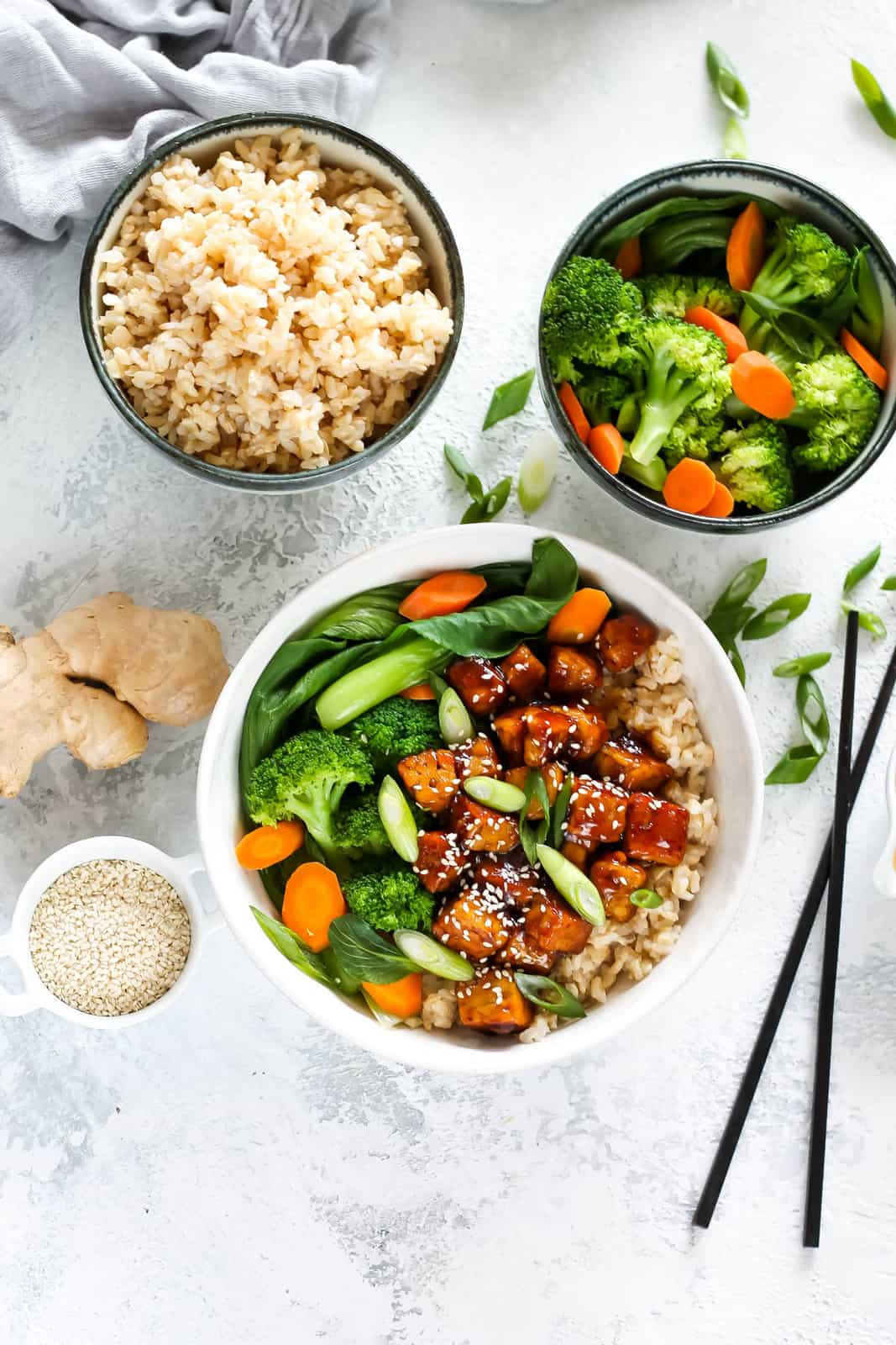 overhead photo of teriyaki tempeh in a white bowl with brown rice and steamed vegetables