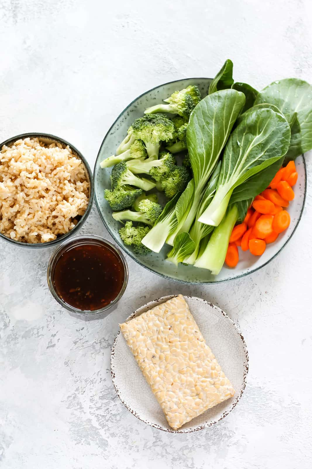 tempeh, teriyaki sauce, brown rice, and a plate of mixed vegetables on a grey background