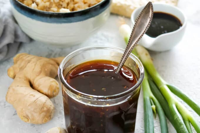 a glass jar of vegan teriyaki sauce with a bowl of rice and some ginger and garlic in the background