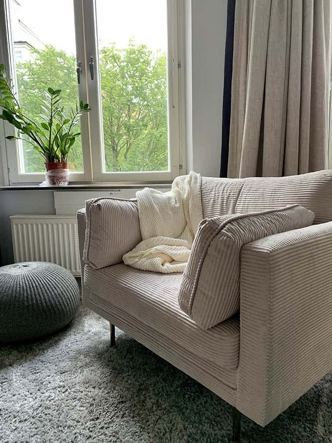 a white chair beside a living room window