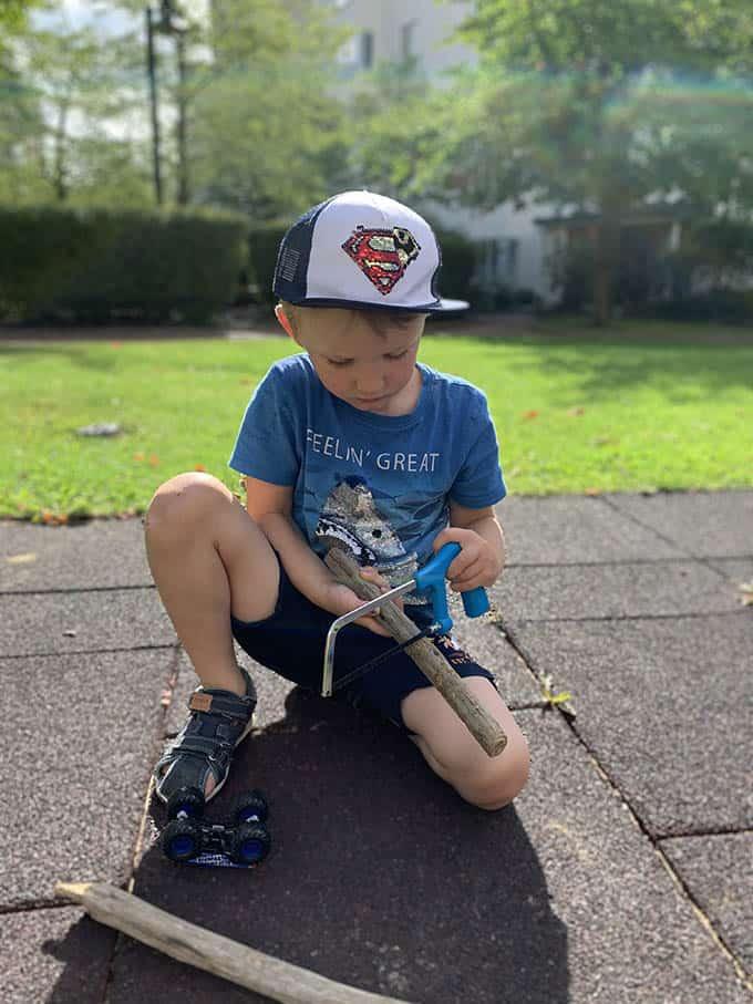 a boy wearing a blue shirt and a baseball hat using a small hack saw on a stick