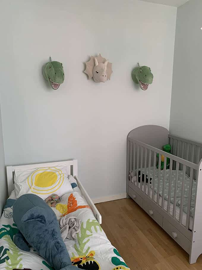 a kid's room with three dinosaur heads on the wall