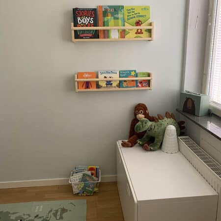 a corner of a child's room with bookshelves and a reading bench