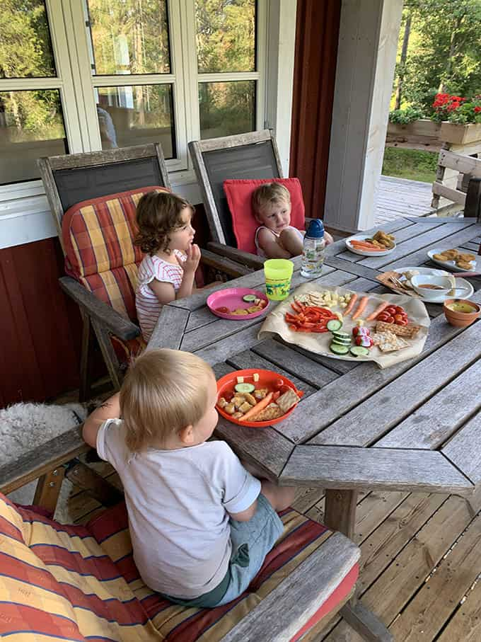 three kids eating a plate of snacks at a wooden table