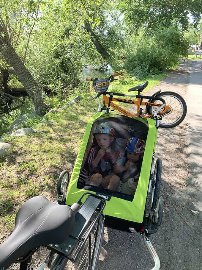 two kids in a green bike chariot with an orange bike strapped to the back
