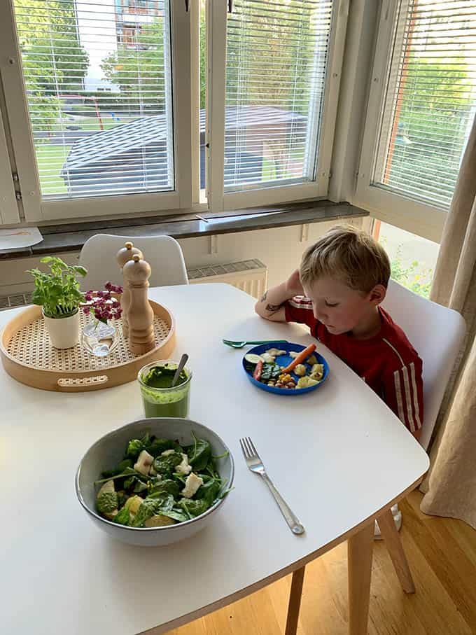 a boy sitting at the table staring woefully at a plate of food
