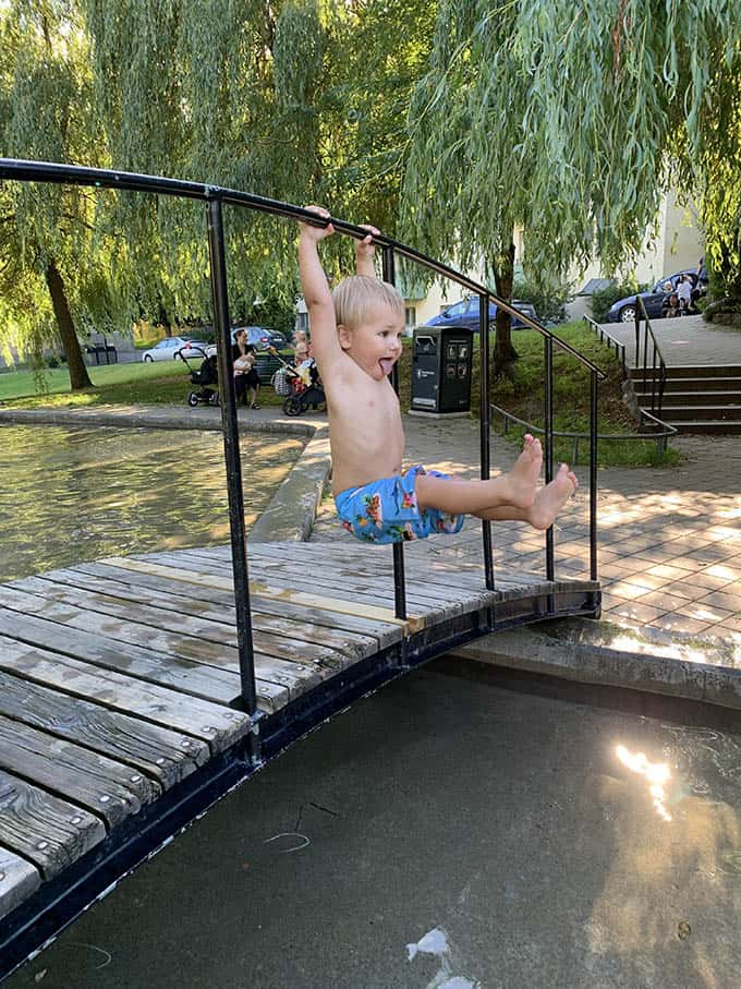 a boy swinging from a wooden bridge at a splash pool