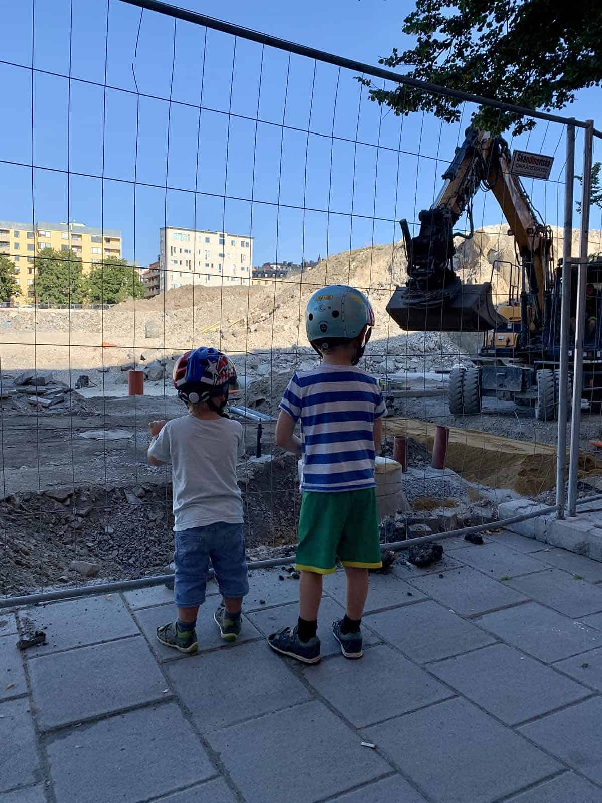 two boys watching machines in a construction site