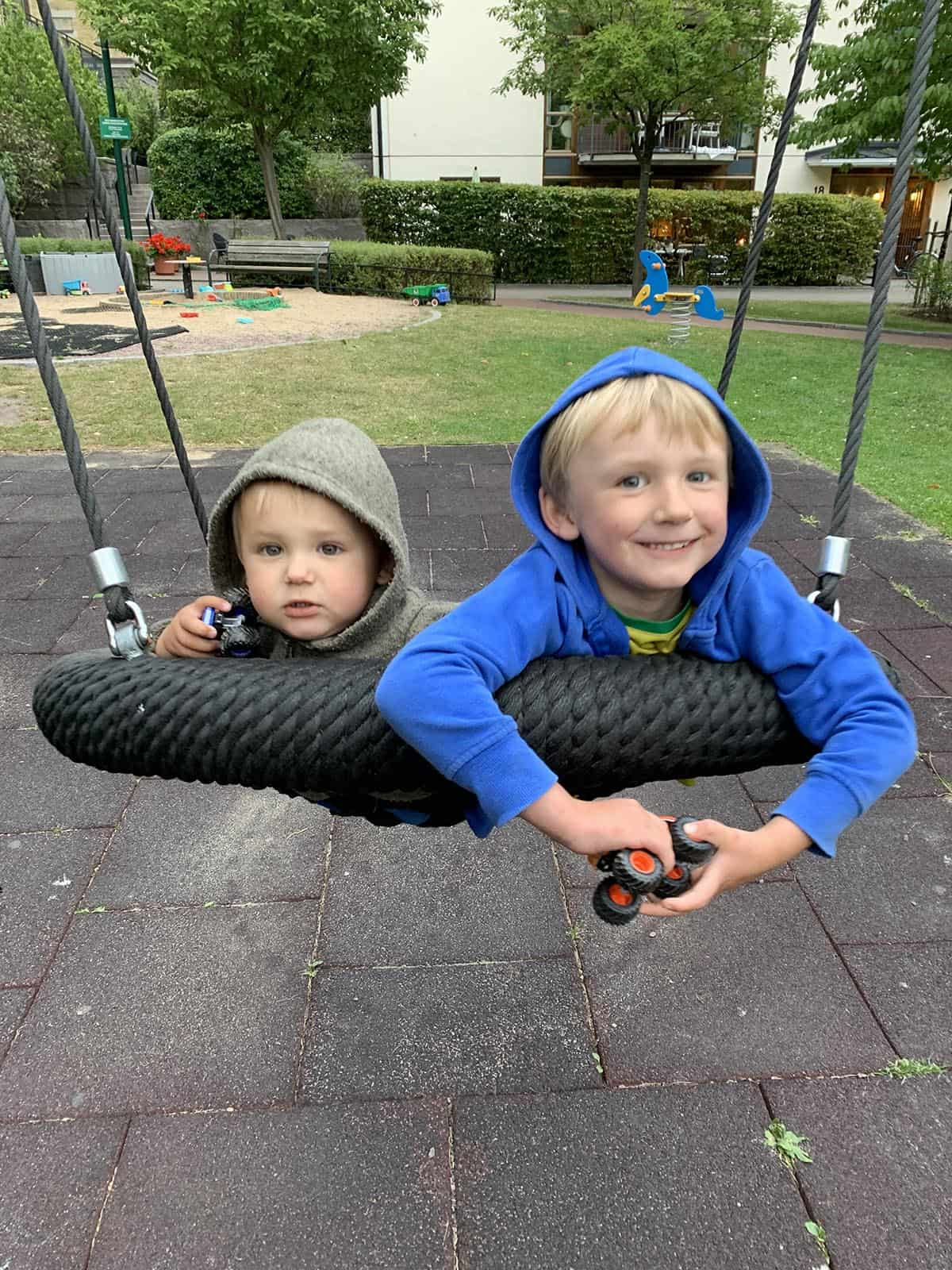 two boys on a big round swing