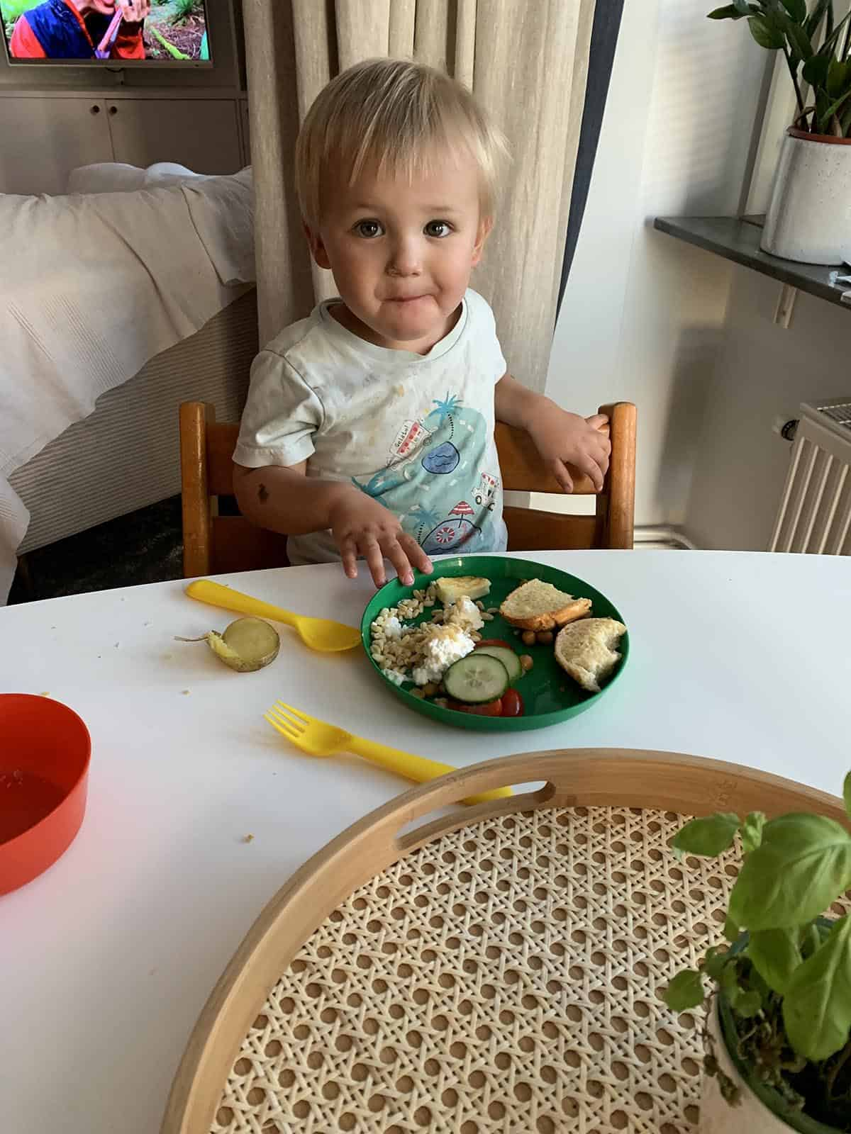 A small boy sitting at a table with a plate of food