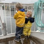 two boys in rain gear standing on a passenger ferry