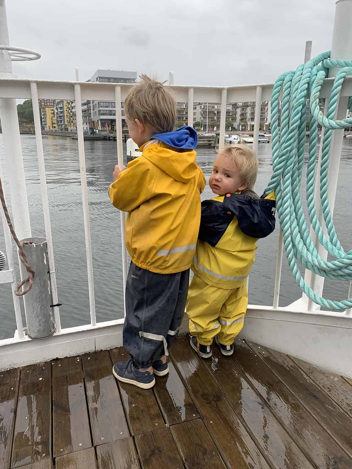 two boys wearing yellow rain suits standing on a ferry boat