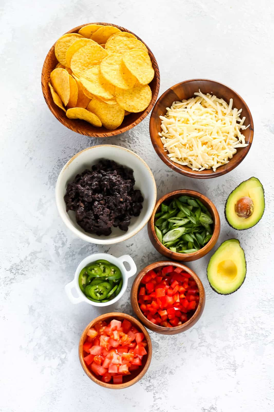 nacho chips, cheese, black beans, avocado, diced tomato, diced red pepper, green onion, and sliced jalapenos on a grey background