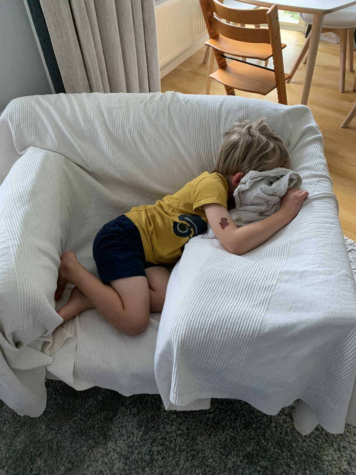 a small boy sleeping on a white armchair