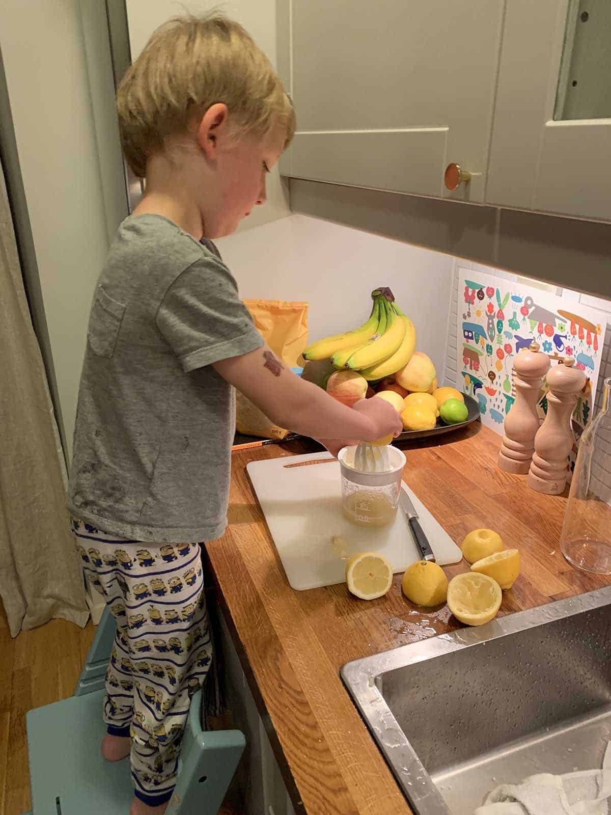 a blond boy juicing lemons